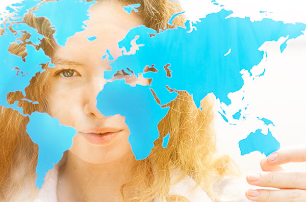 Image of a world map juxtaposed over a young woman's face.